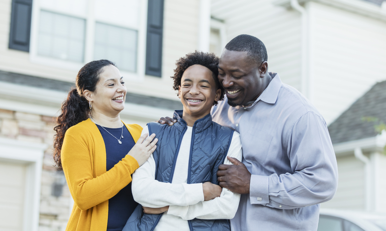 A 14 year old mixed race Hispanic and African-American teenage boy standing between his parents outside their home. Mom is a mature Hispanic woman and dad is a mature African-American man. They are both in their 40s, happy and proud of their son.