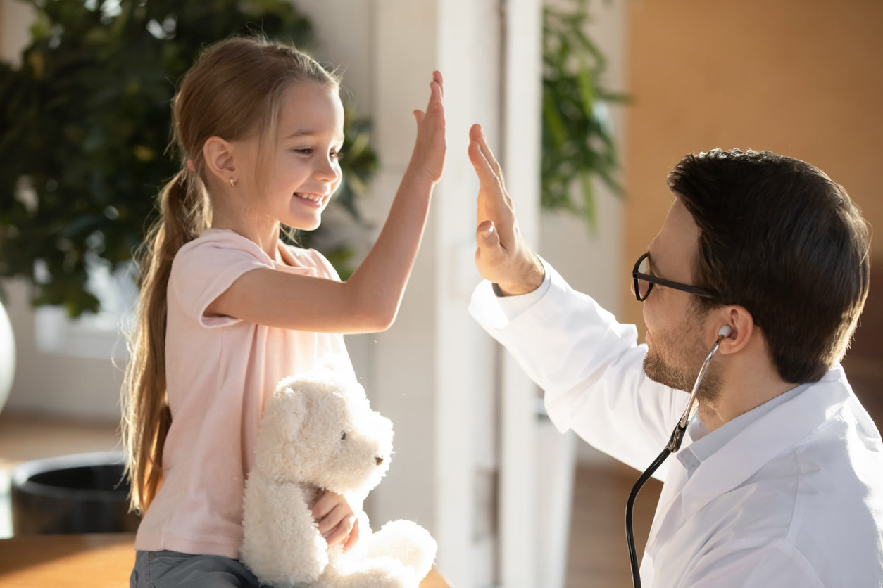 Happy little patient giving high five to pleasant male doctor.